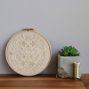 an image of an embroidery hoop with a floral monochrome pattern against a beige wall and a succulent