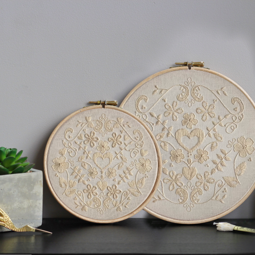 a 15cm and a 20cm embroidery hoop with a cream monochrome floral design against a beige wall next to a succulent and a pair of scissors